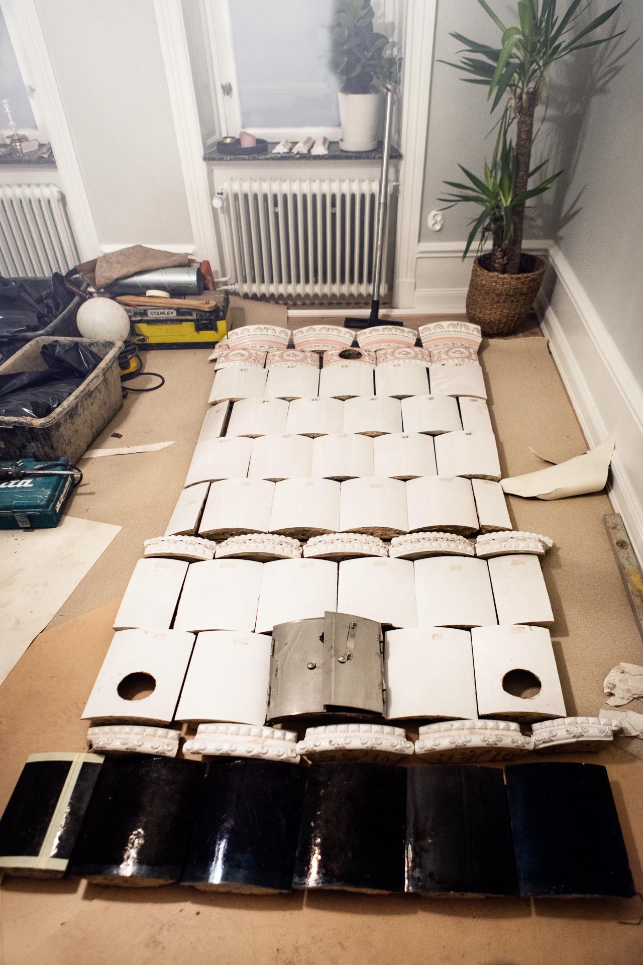 Kakelugnen läggs ut på golvet för att kontrollera att den är komplett.  Många bitar blir det...